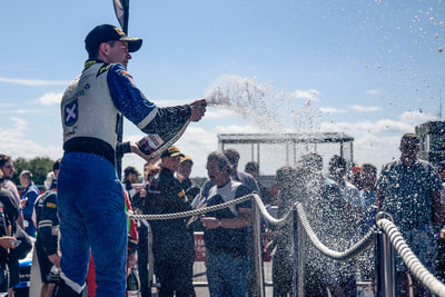Ecurie Ecosse celebrate race win with champagne